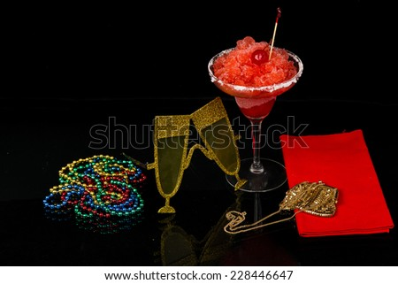 Colorful glasses, beads; gold purse and strawberry margarita against black background create high contrast party atmosphere. - stock photo