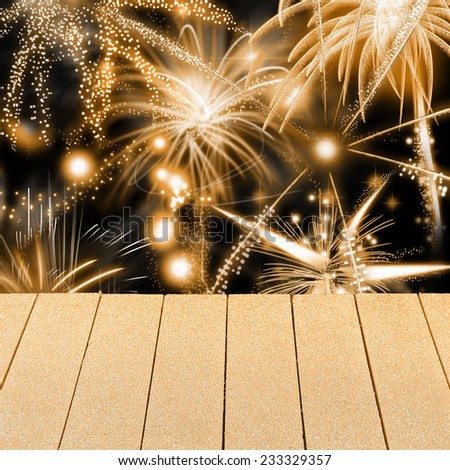 Colorful golden New Year or Holiday fireworks display with bursting rockets in a night sky with an empty wooden table in the foreground for product placement or presentation - stock photo