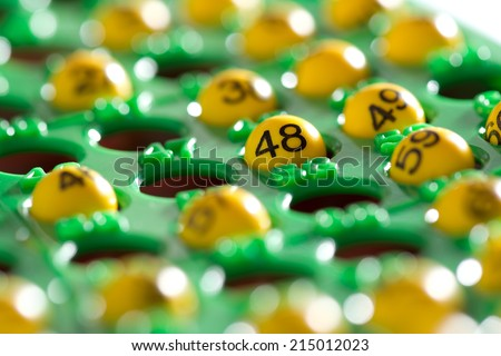 Colorful green bingo board half filled with lucky numbers on yellow plastic balls during a game of bingo , low angle view  - stock photo