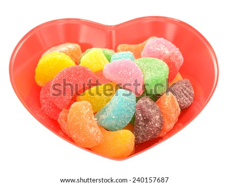 colorful gummy candies in plastic heart shape bowl isolated on white  - stock photo