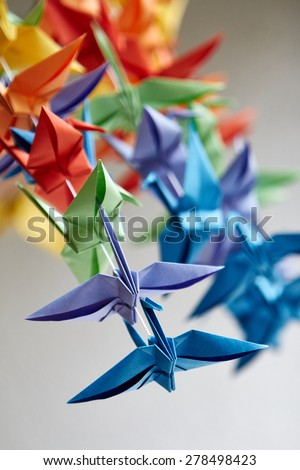Colorful handmade origami cranes or fantasy birds, made of folded paper with complementary different colors, concept of joy, creativity and simplicity, close-up on gray - stock photo