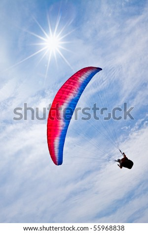 Colorful hang glider in sunny sky - stock photo