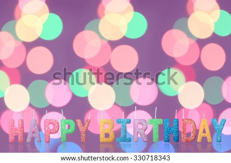 Colorful happy birthday candles with blur background. - stock photo