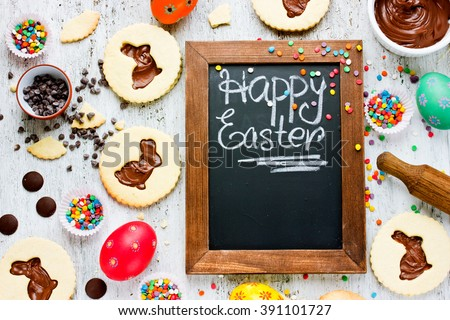 Colorful Happy Easter baking background. Cute idea for child sweets treats on holiday egg cookies sprinkling chocolate top view - stock photo