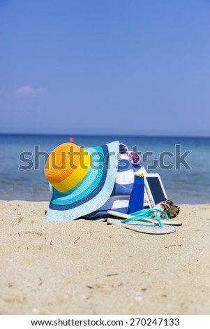 Colorful hat and bag on the beach - stock photo