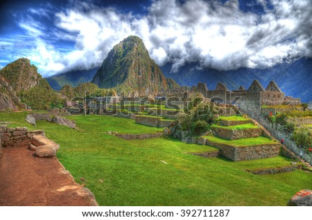 Colorful HDR image of tourists visiting the ruins in Machu Picchu, the lost Incan City of Machu Picchu near Cusco, on a clear blue sky - stock photo