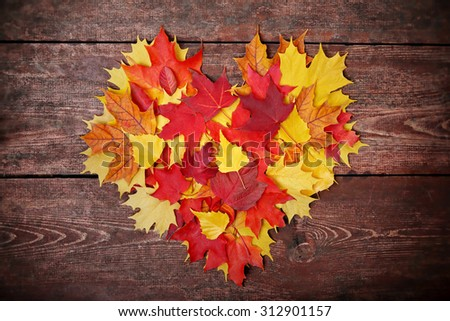 Colorful heart made of autumn leaves on a wooden background - stock photo