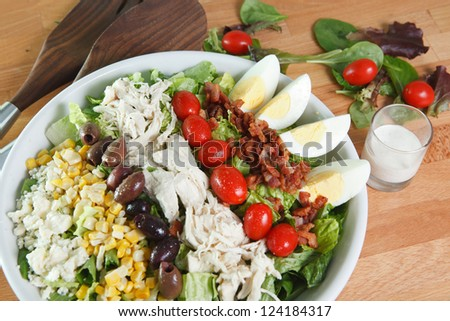 Colorful hearty entree sized cobb salad with bacon, chicken, boiled eggs, corn, olives, romaine lettuce and much more. - stock photo