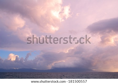 Colorful heavy clouds above land and sea water - stock photo