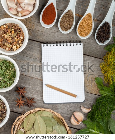 Colorful herbs and spices selection. Aromatic ingredients on wood table with blank notepad - stock photo