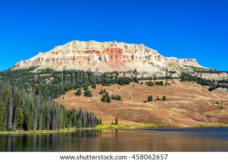 Colorful hill rising above a peaceful lake in Shoshone National Forest in Wyoming - stock photo