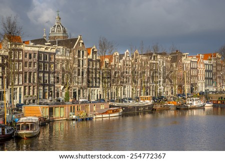Colorful historic canal houses and houseboats on the kromme waal in I Amsterdam - stock photo