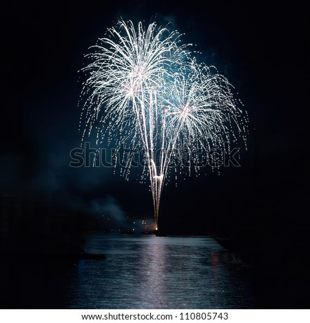 Colorful holiday fireworks on the black sky background. - stock photo
