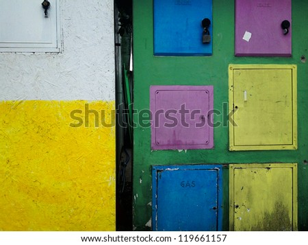 Colorful home gas counter boxes - Italy. - stock photo