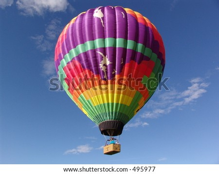 Colorful hot air balloon and basket, rising in the blue sky - stock photo