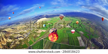 Colorful hot air balloon flying over rock landscape in  blue sky  at Cappadocia Turkey  - stock photo