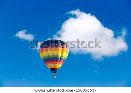 Colorful hot air balloon over blue sky - stock photo