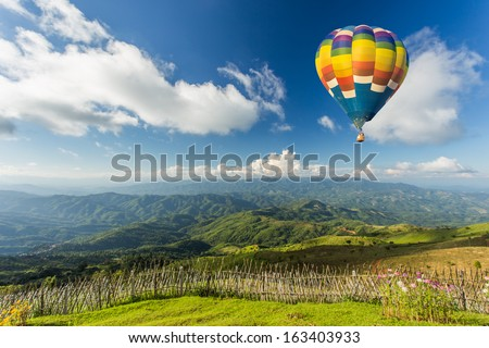 Colorful hot air balloon over the mountain - stock photo