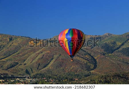 Colorful hot air balloon with autumn colors in the mountains above Park City, Utah, USA. - stock photo