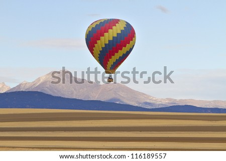 Colorful Hot air balloon with the stripes of agriculture farmlands in the foreground and the Twin Peaks, Mt Meeker 13,911 feet and Longs Peak 14,256 feet. - stock photo