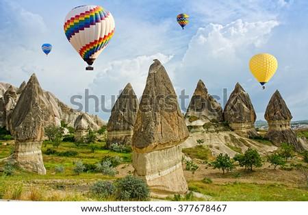 Colorful hot air balloons flying over volcanic cliffs at Cappadocia, Anatolia, Turkey. - stock photo
