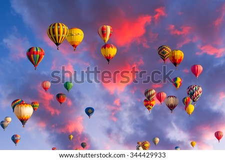 Colorful hot air balloons in flight  illuminated by early morning light - stock photo