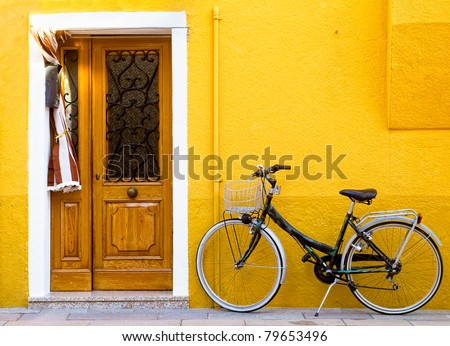 Colorful house on the island of Burano with a bike near the entrance - stock photo