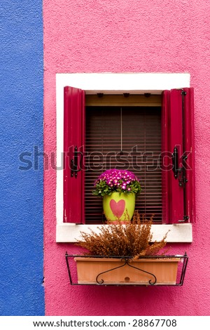 Colorful house with window, shutters flowers and plants - stock photo
