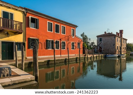 Colorful houses along a canal on Torcello island in Venice lagoon, Italy - stock photo