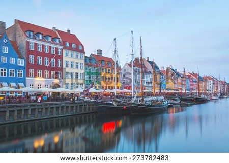 Colorful houses in Copenhagen old town, with boats and ships in the canal in front of them. Long exposure shot in late afternoon. - stock photo