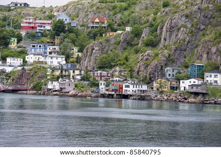Colorful houses on the rocky shore of Signal Hill facing the harbour in St. John's, Newfoundland, Canada.  A section of town known as the Lower Battery. - stock photo
