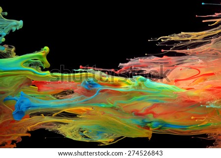 Colorful ink swirling through water - stock photo