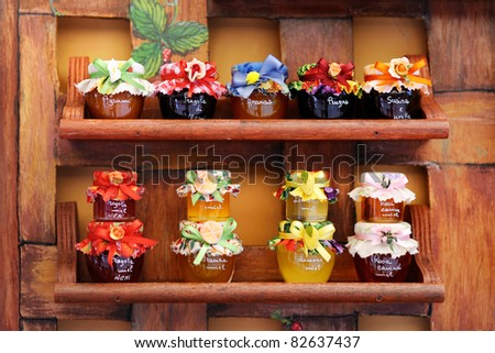 Colorful jam jars arranged for sale - stock photo