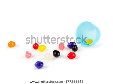 Colorful jelly beans spilled out of a blue plastic Easter egg. - stock photo
