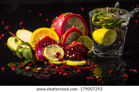 Colorful juicy assortment of sliced tropical fruits (purple dragon fruit, orange, lemon, pomegranate seeds, green apple and mint), on a wet black table, with a glass of transparent water - stock photo