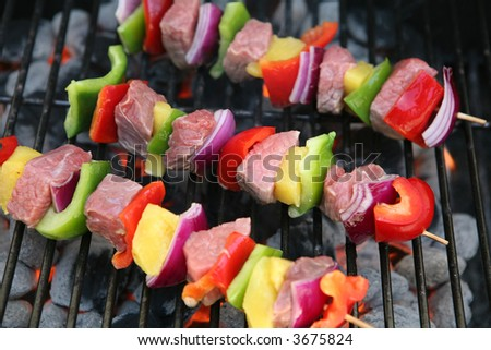 Colorful kabobs cooking on the grill with meat and vegetables - stock photo