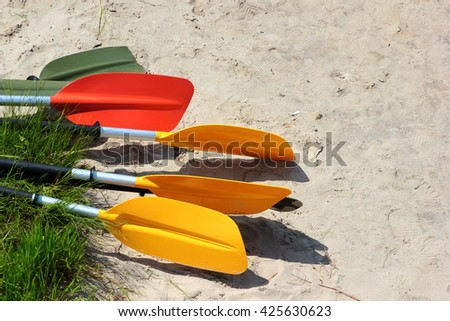 Colorful kayak paddles and oars on sandy beach - stock photo