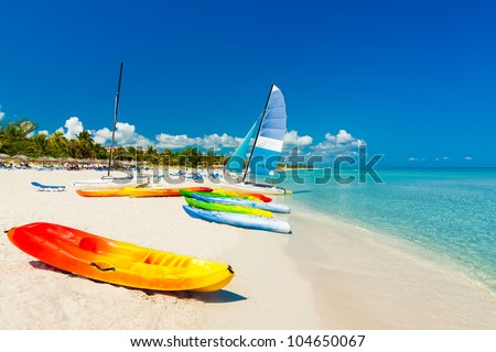 Colorful kayaks and sailing boats on a tropical beach in Cuba - stock photo