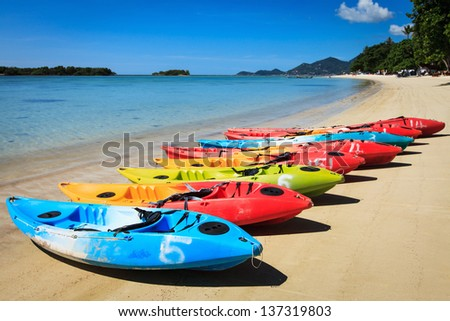 Colorful kayaks on sandy beach. - stock photo