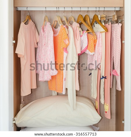 colorful kid's clothes hanging on bar in wooden wardrobe with pillows - stock photo