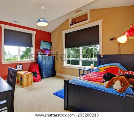 Colorful kids room with beige and red walls. Furnished with single bed and desk - stock photo