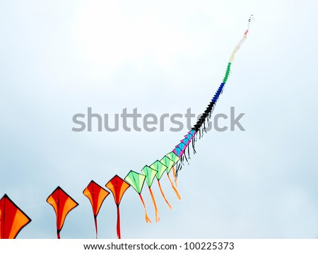 Colorful kites flying in the cloudy sky - stock photo