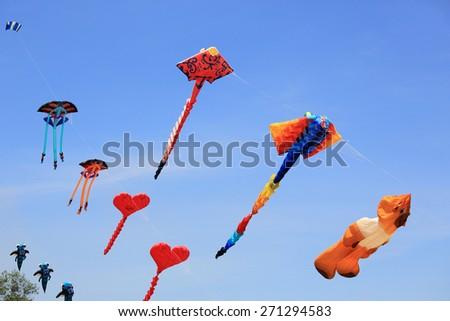 Colorful kites in blue sky.  - stock photo