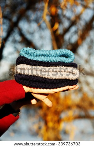 Colorful knitted woolen warm hats in female hands. Bright stylish photo.  - stock photo