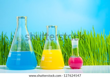 Colorful lab tubes and flasks with spring fresh bright green grass on background - stock photo
