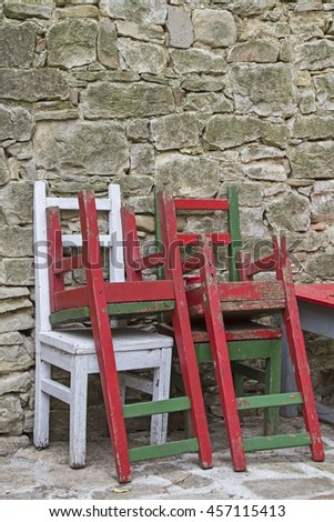 Colorful lacquered chairs parked near a stone wall - stock photo