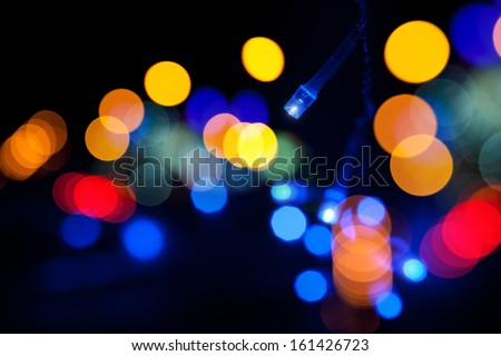 Colorful LED (light emitting diodes) lights garland with bokeh effect on black background - stock photo