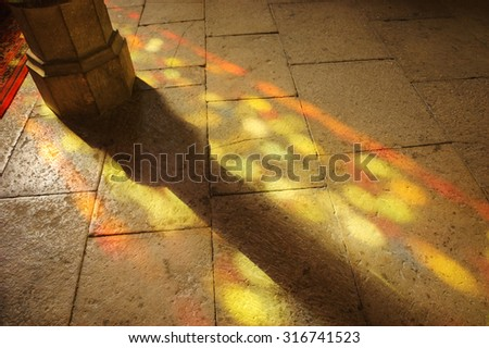 Colorful light spots on the the floor in church. Sunlight filtered through the stained glass window. A game of light and shadow. - stock photo