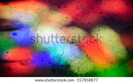 Colorful light spots on the tiled floor. Sunlight filtered through the stained glass window. - stock photo
