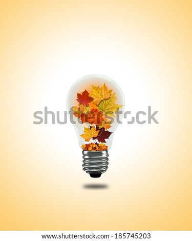 Colorful lightbulb with autumn leaves - stock photo